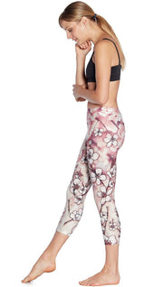 left side view of model wearing cherry blossom themed printed capri leggings and sports top