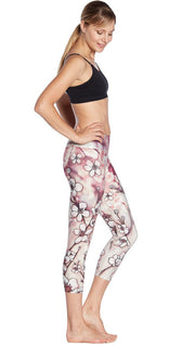 right side view of model wearing cherry blossom themed printed capri leggings and sports top