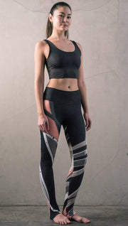 slightly turned front view of model wearing striped coral moto themed printed full length leggings