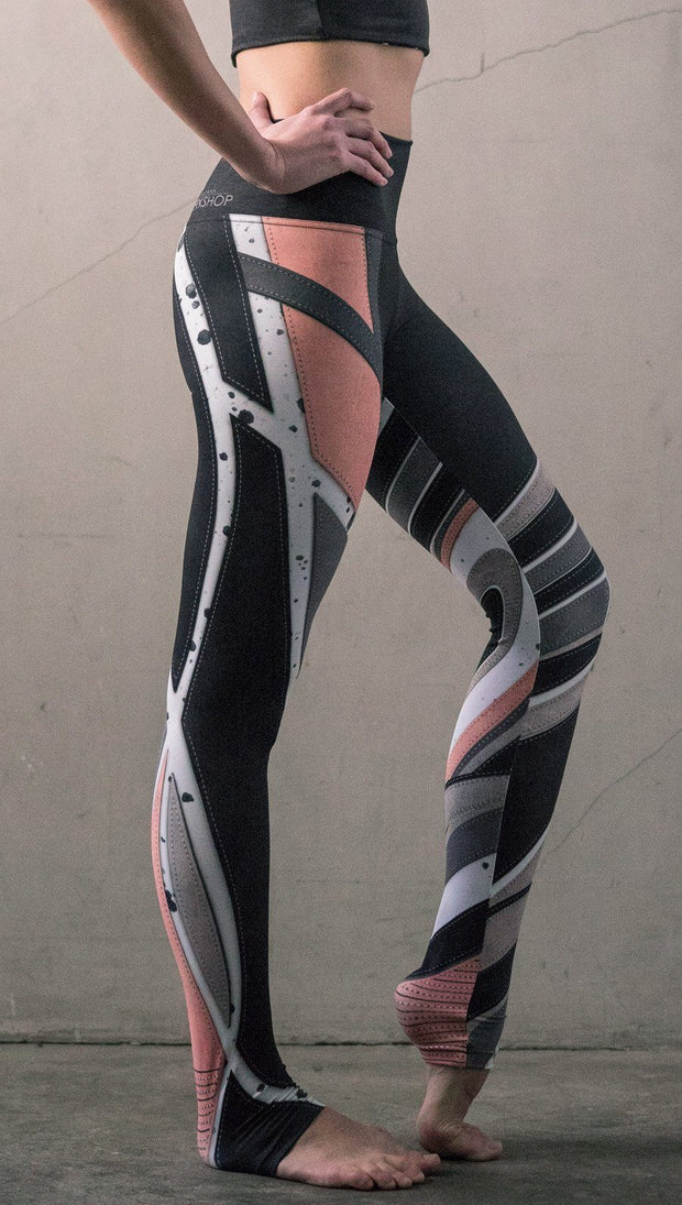 closeup right side view of model wearing striped coral moto themed printed full length leggings