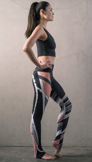 right side view of model wearing striped coral moto themed printed full length leggings