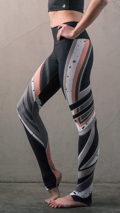 closeup left side view of model wearing striped coral moto themed printed full length leggings