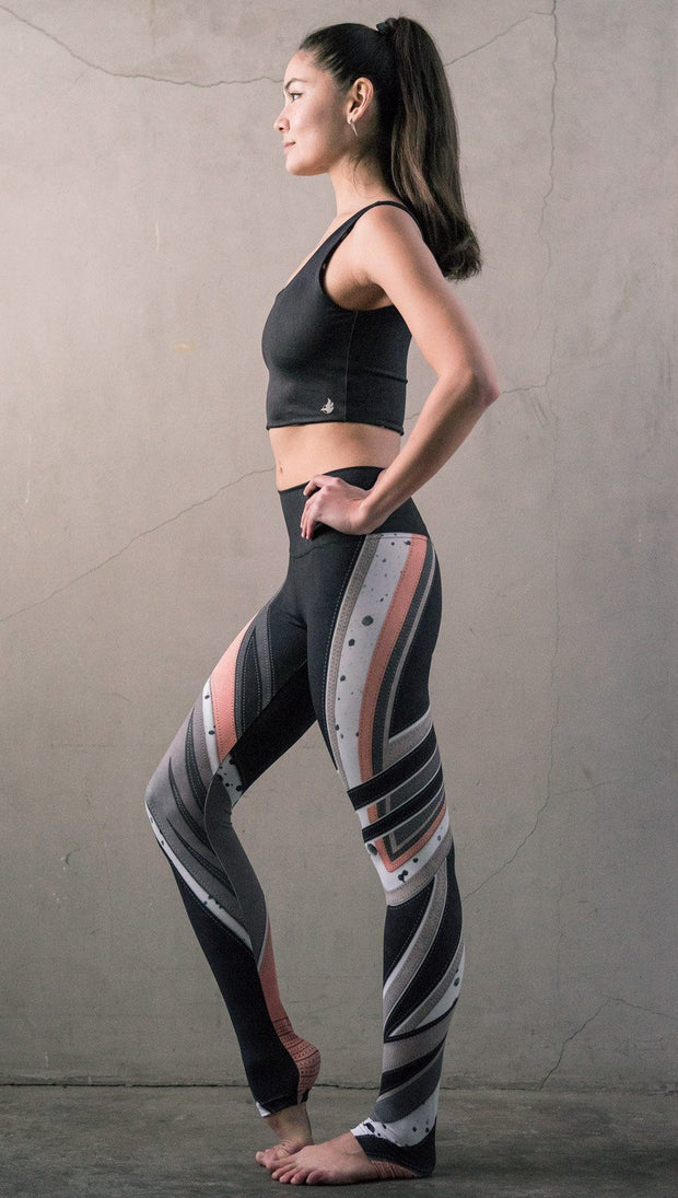 left side view of model wearing striped coral moto themed printed full length leggings