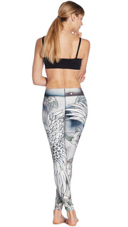 back view of model wearing flying crane themed printed full length leggings