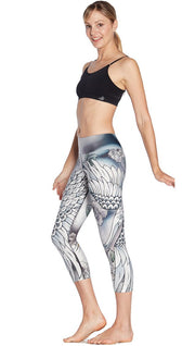 left side view of model wearing flying crane themed printed capri leggings