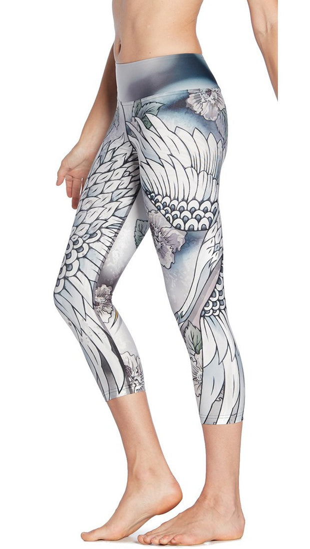 close up left side view of model wearing flying crane themed printed capri leggings