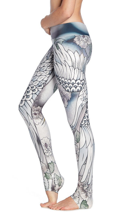 close up left side view of model wearing flying crane themed printed full length leggings