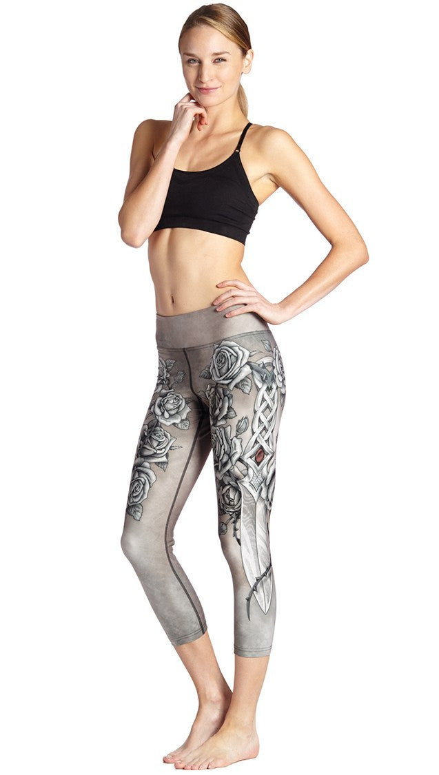 close up side view of sword and roses themed printed capri leggings