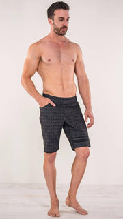 Front view of model wearing charcoal black printed performance shorts with slim fit and distressed tribal inspired art