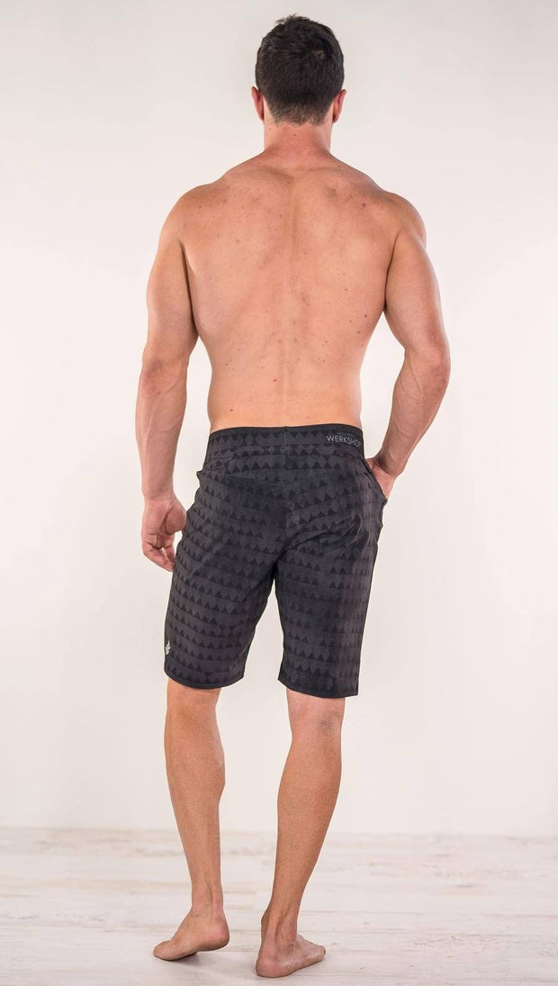 Back view of model wearing charcoal black printed performance shorts with slim fit and distressed tribal inspired art