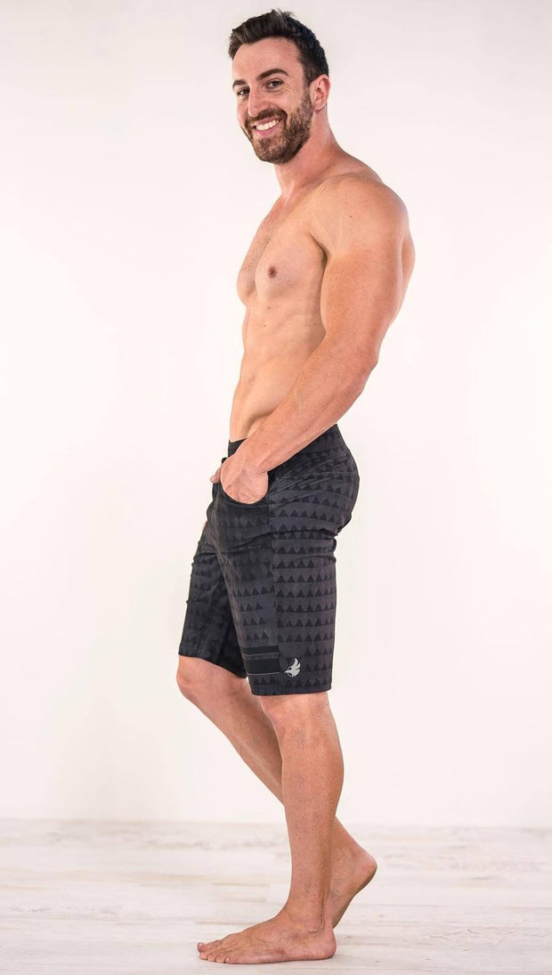 Left side view of model wearing charcoal black printed performance shorts with slim fit and distressed tribal inspired art