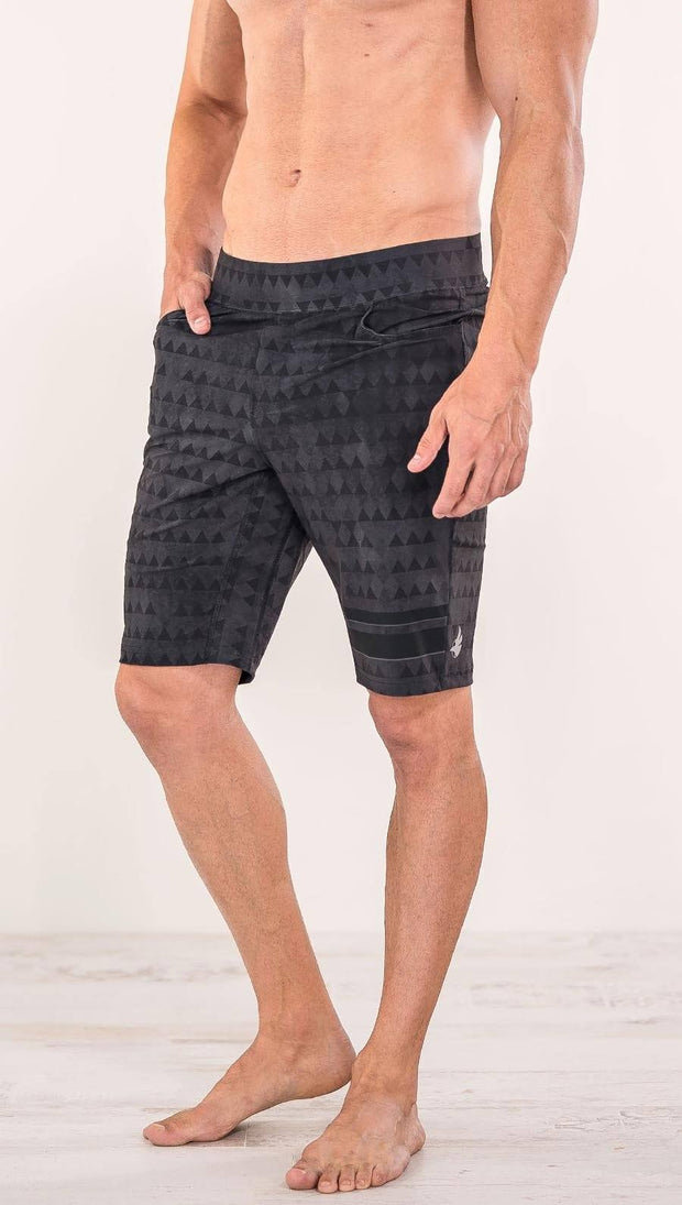 Close up front view of model wearing charcoal black printed performance shorts with slim fit and distressed tribal inspired art