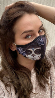 girl wearing a gray face mask with sugar skull artwork on one side