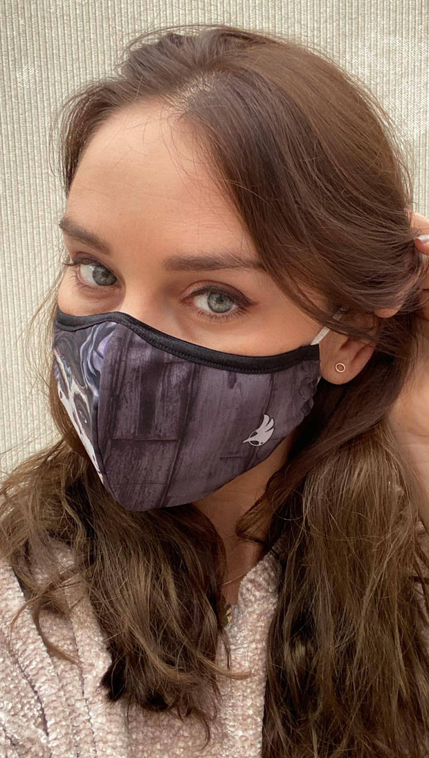 girl wearing a gray face mask with sugar skull artwork on one side and wood grain texture on the other side
