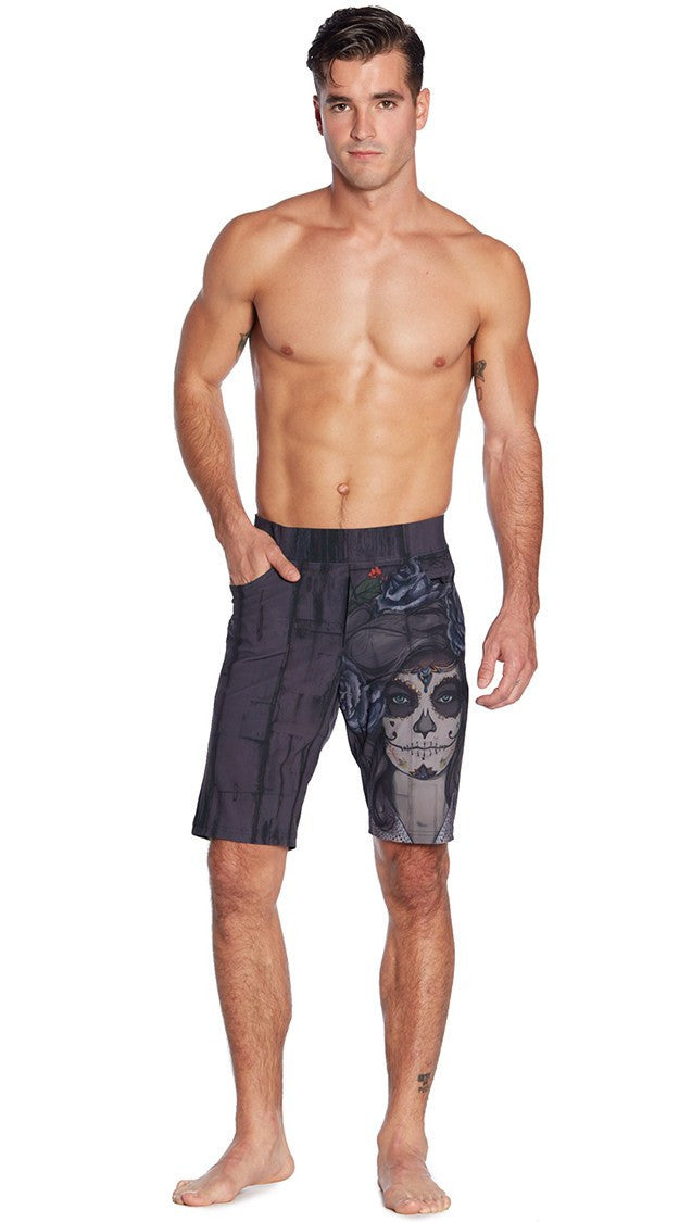 closeup front view of model wearing dark sugar skull inspired printed mens performance shorts