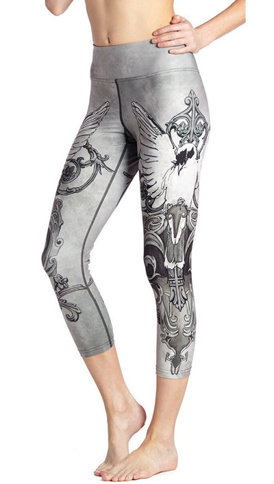 close up side view of black and white fantasy dove themed printed capri leggings