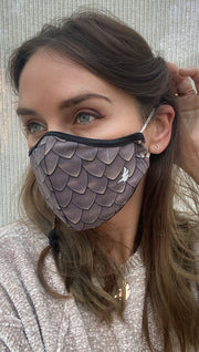 Left side view of model wearing a brown dragon scales mask with the WERKSHOP logo in white on the bottom corner