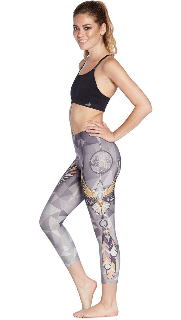 left side view of model wearing dreamcatcher themed printed capri leggings