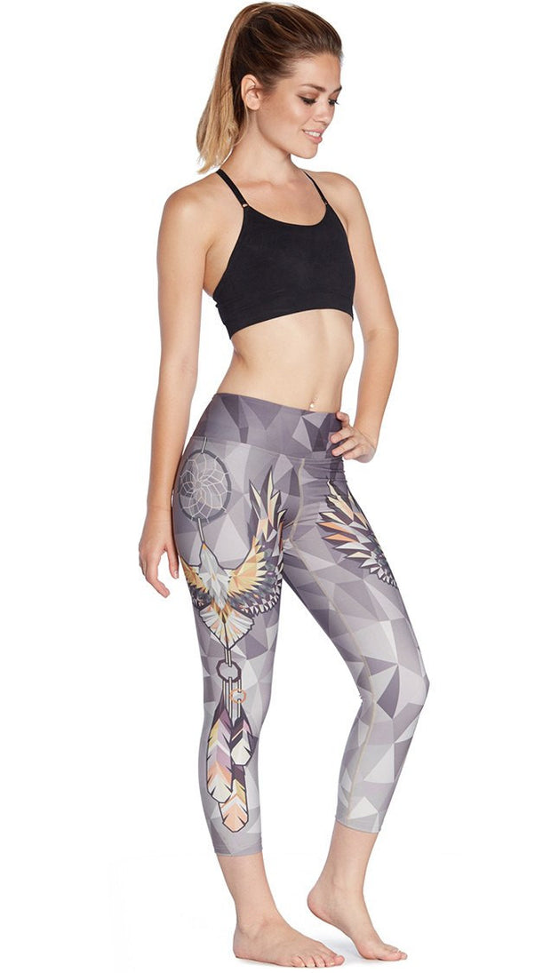 slightly turned front view of model wearing dreamcatcher themed printed capri leggings