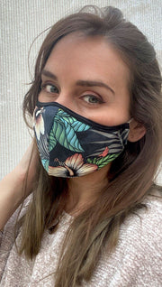 Left view of model wearing a black mask with a tropical floral design and a small WERKSHOP logo in red at the bottom corner