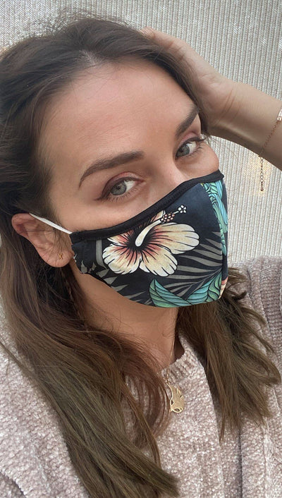 Right side view of model wearing a black mask with a tropical floral design