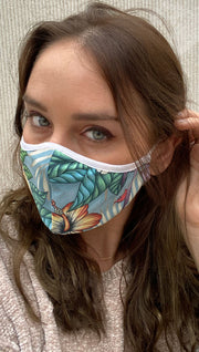 girl wearing face mask with light blue tropical/floral artwork