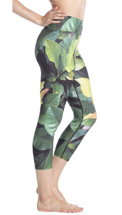 close up side view of tropical foliage themed printed capri leggings