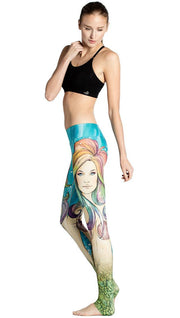left side view of model wearing colorful mermaid face themed printed full length leggings