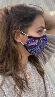 Right side view of model wearing a purple frosting mask with colorful sprinkles