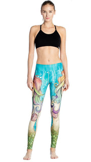 front view of model wearing colorful mermaid face themed printed full length leggings