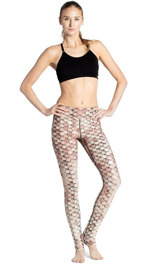 front view of model wearing gold mermaid scale themed printed full length leggings