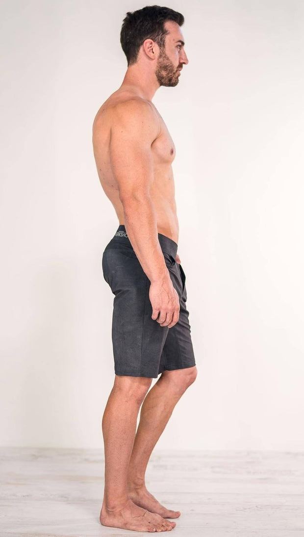 Right side view of model wearing gray men's performance shorts