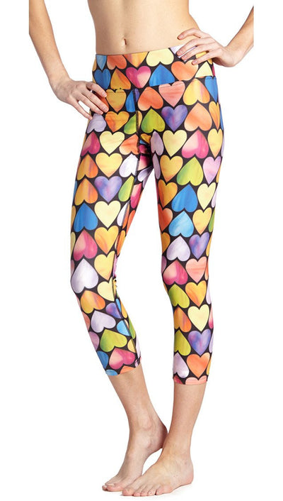 close up side view of colorful heart themed printed capri leggings