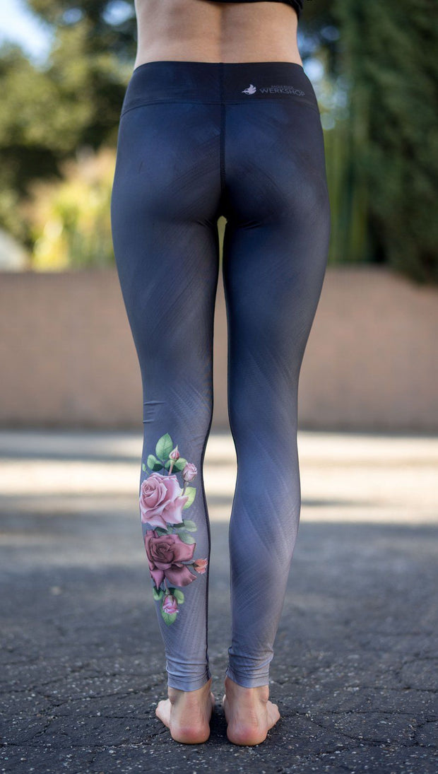 close up back view of model wearing rose themed full length leggings