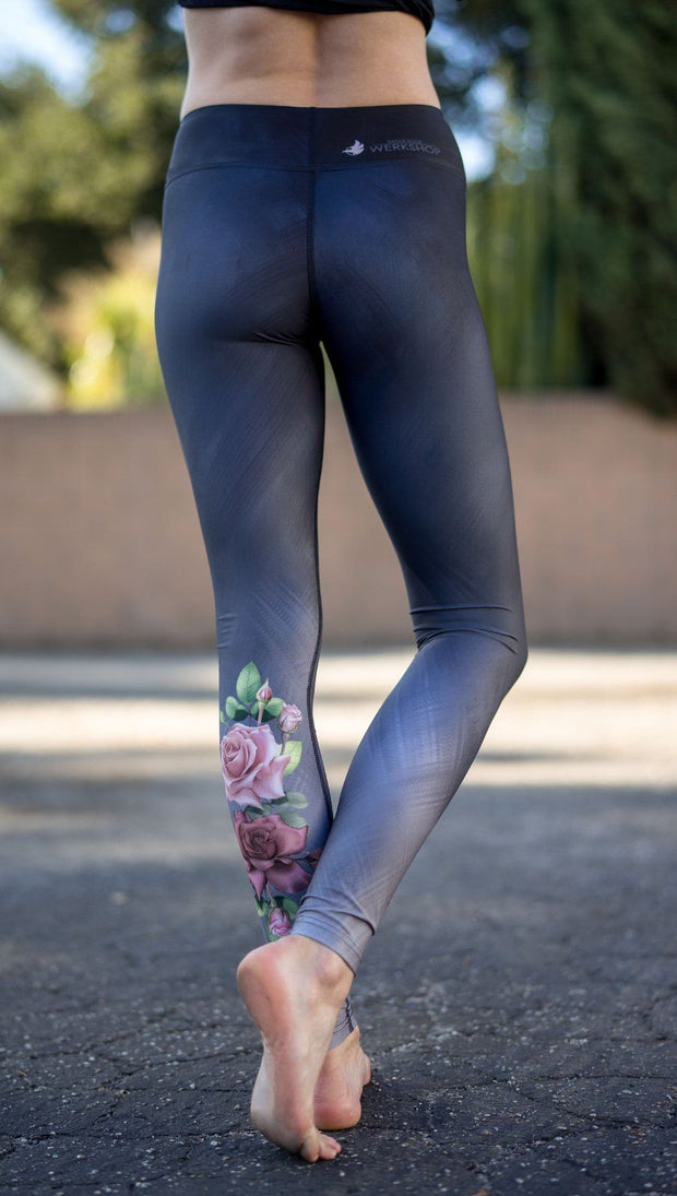 closeup back view of model wearing rose themed full length leggings