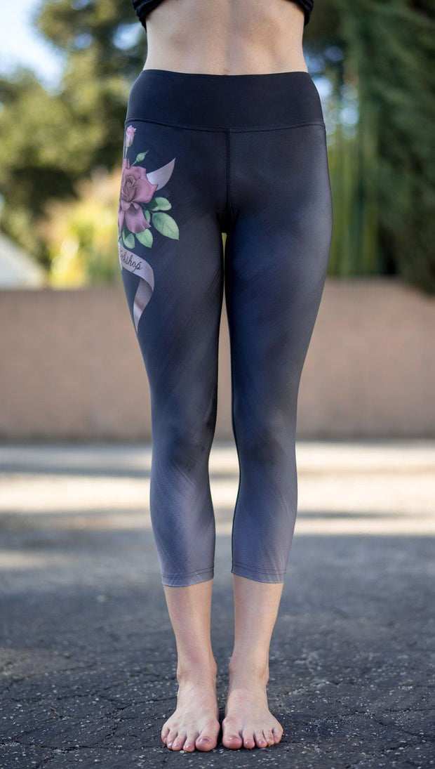 closeup front view of model wearing rose themed capri leggings