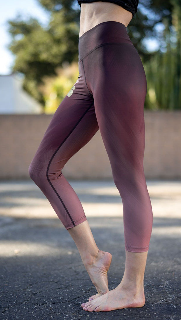 closeup left side view of model wearing tattoo rose design printed capri leggings
