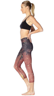 left side view of model wearing honeycomb galaxy themed printed capri leggings