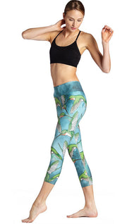 left side view of model wearing flying hummingbird themed printed capri leggings