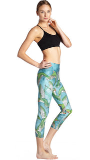 right side view of model wearing flying hummingbird themed printed capri leggings
