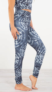 Right side view of model wearing the indigo circles athleisure leggings. They are in a indigo color and have white tie dye circles throughout. Each circle has a smaller circle within each other.