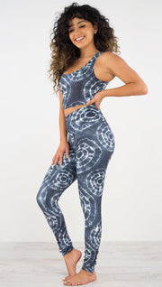 Left side view of model wearing the indigo circles athleisure leggings. They are in a indigo color and have white tie dye circles throughout. Each circle has a smaller circle within each other.