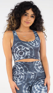 Front view of model wearing the reversible indigo circles/ stripes crop top. This is the circles side. It is in a indigo color with white tie dye circles throughout. Each circle has a smaller circle within each other.