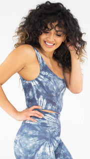 Right side view of model wearing the reversible indigo waves/ spiral crop top. This is the spiral side. It is in a indigo color and has white tie dye spirals throughout the top.