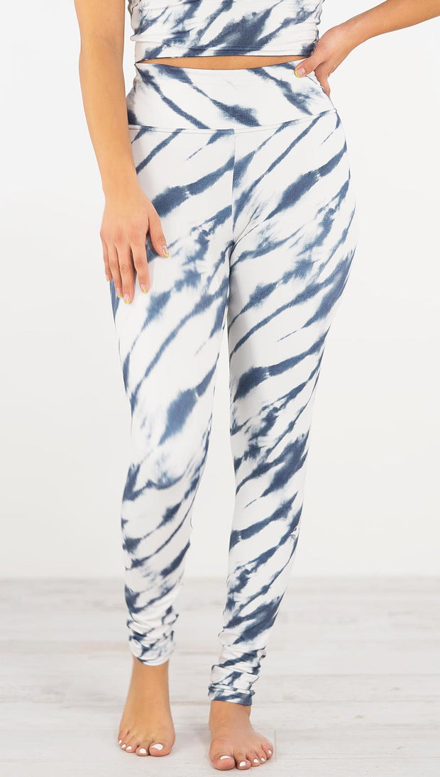 Front view of model wearing the indigo stripes athleisure leggings. They are in a white color with blue zebra-like stripes.