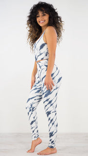 Left side view of model wearing the indigo stripes athleisure leggings. they are in a white color and have blue zebra-like stripes.