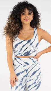 Front view of model wearing the reversible indigo circles/ stripes crop top. This in the stripes side. It is in a white color with blue zebra-like stripes.