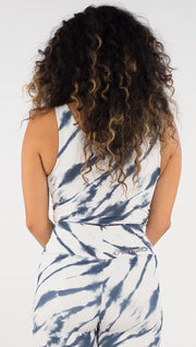 Back view of model wearing the reversible indigo circles/ stripes crop top. This is the stripes side. It is in a white color with blue zebra-like stripes.