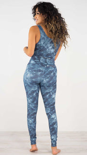 Back view of model wearing the indigo waves athleisure leggings. They are in a indigo color and have a water waves print in a white and navy color throughout.