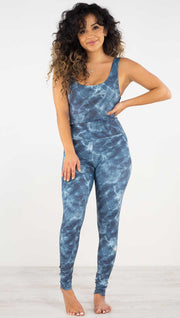Front view of model wearing the indigo waves athleisure leggings. They are in a indigo color and have a water waves print in white and navy color throughout.